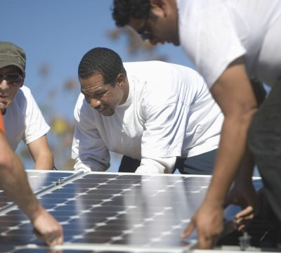 engineers placing solar panel on rooftop