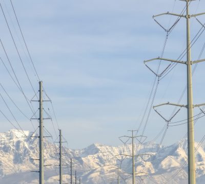 Power lines against Mount Timpanogos and blue sky. Overhead power lines against Mount Timpanogos and peaceul blue sky in Eagle Mountain, Utah. The majestic mountain is blanketed with sunlit snow.