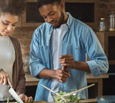 Loving african-american couple preparing vegetable salad in loft kitchen